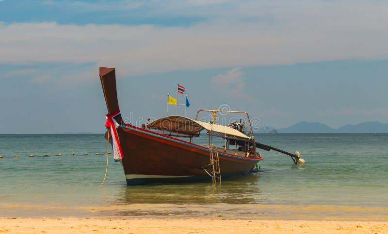 Le bateau en bois traditionnel tha?landais de longue queue et la montagne en pierre est situ? ? la belle mer Eau propre de plage  photo libre de droits