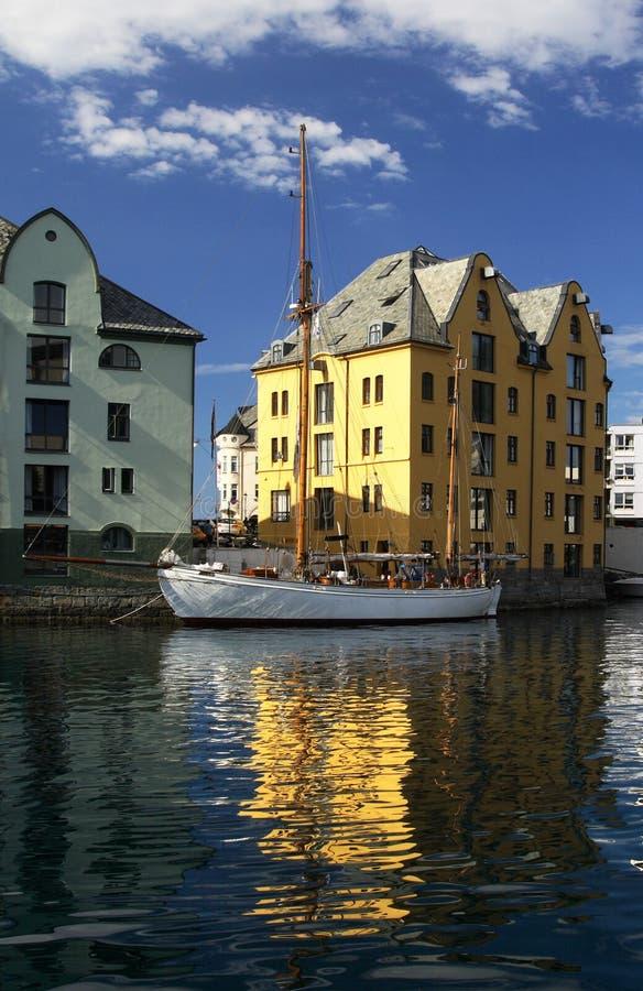 Le bateau et la maison grands ont reflété - Alesund, Norvège photos stock