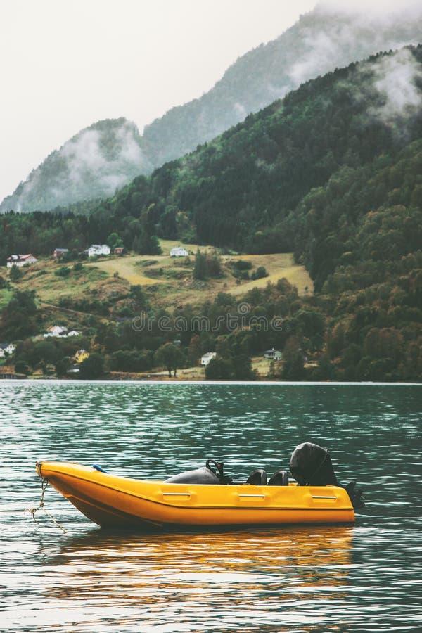 Le bateau jaune dans le fjord de mer et les montagnes aménagent en parc image stock