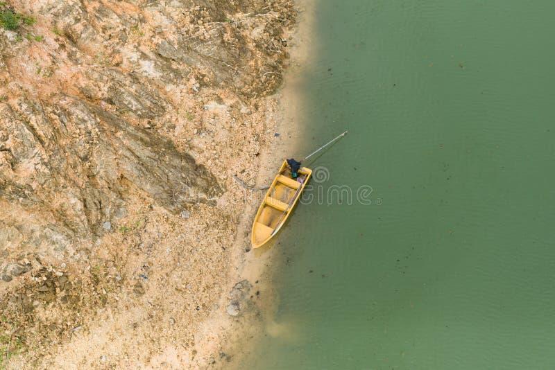Le bateau jaune est garé sur la rive verte de l'eau images stock