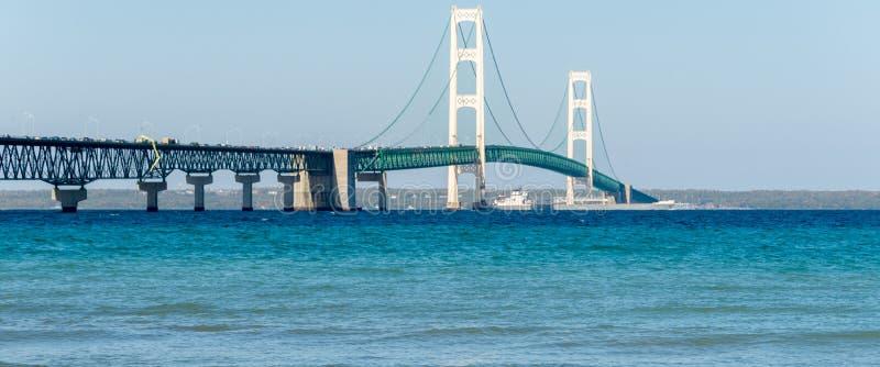 Le bateau passe sous le pont de Mackinac au Michigan images stock