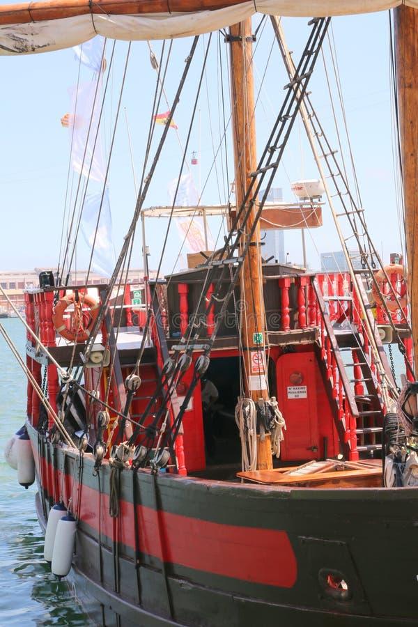 Le bateau rouge se déplace vers le dock au port image stock