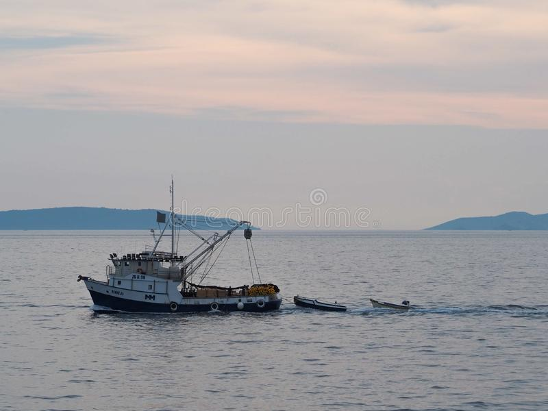 Le bateau tire deux plus petits bateaux avec effort en mer photo libre de droits