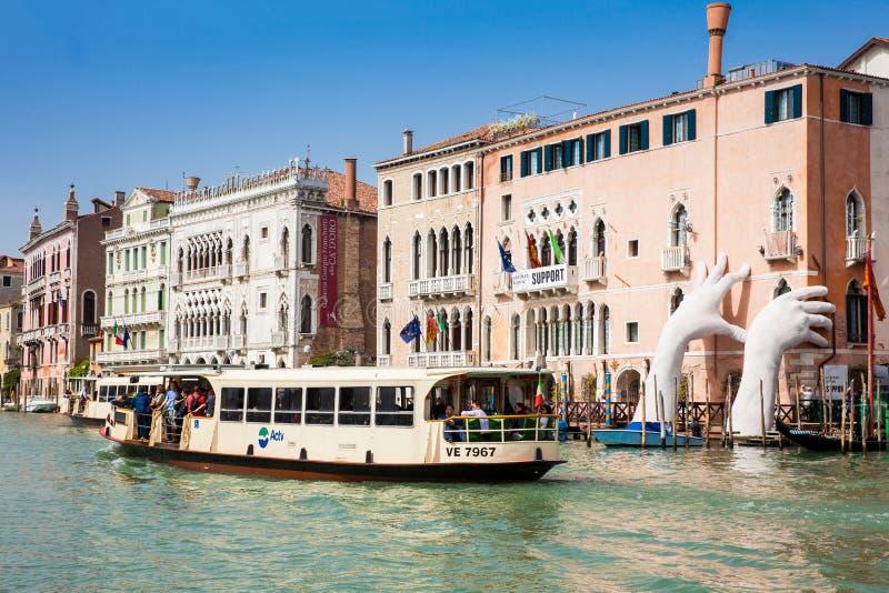 Le bateau touristique passant par la sculpture en mains a créé par l'artiste espagnol Lorenzo Quinn à Venise Grand Canal pour fai image libre de droits
