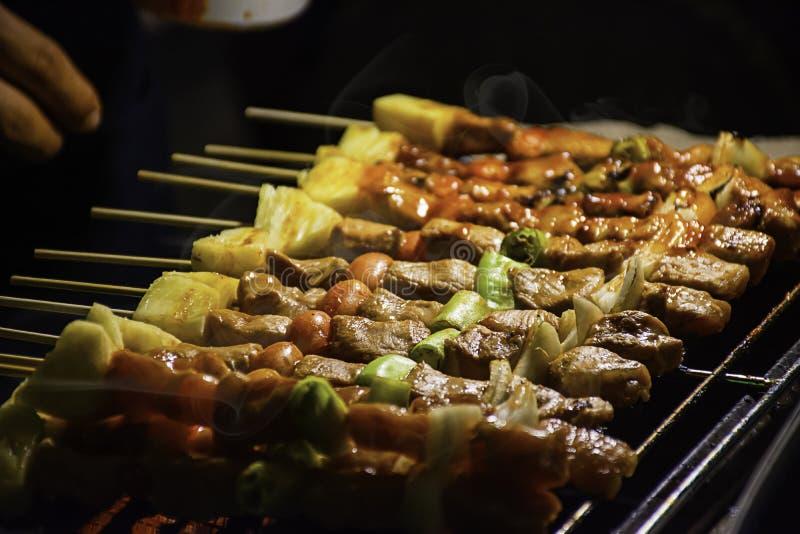 Le BBQ a grillé la viande avec les sauces de légume et tomate sur les grils en acier avec la chaleur photo stock