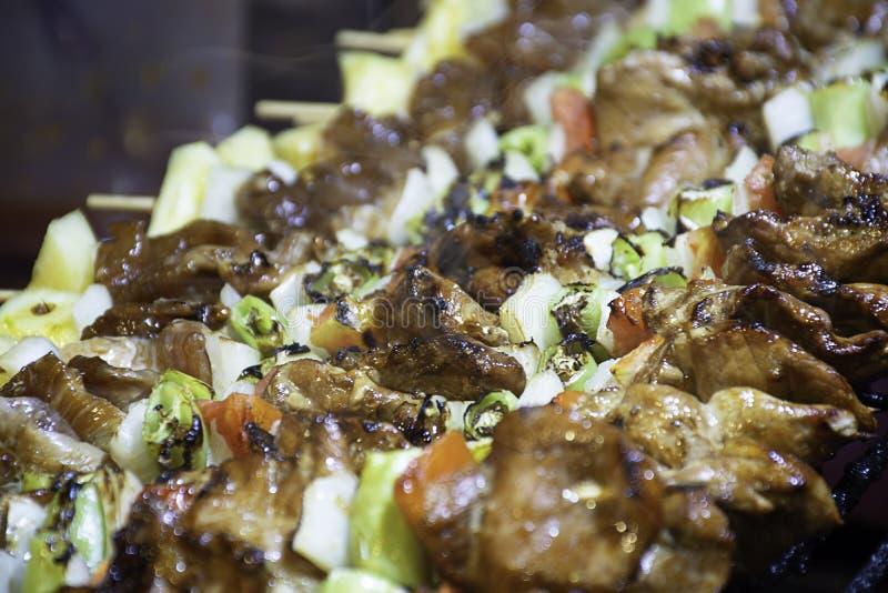 Le BBQ a grillé la viande avec les sauces de légume et tomate sur les grils en acier avec la chaleur photos stock