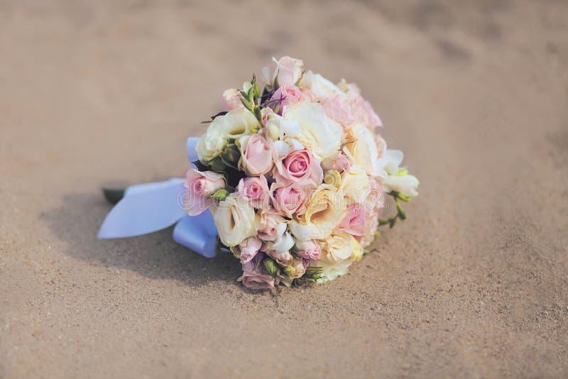 Le beau bouquet de mariage de vintage fleurit la plage de sable de roses photos libres de droits