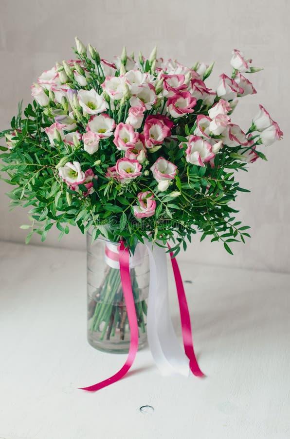 Le beau bouquet romantique de l'eustoma rose et blanc fleurit avec la bande de satin dans un vase sur un fond blanc image libre de droits