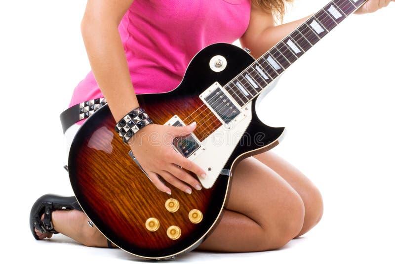 Le beau brunette pose dans le studio avec un guit image stock