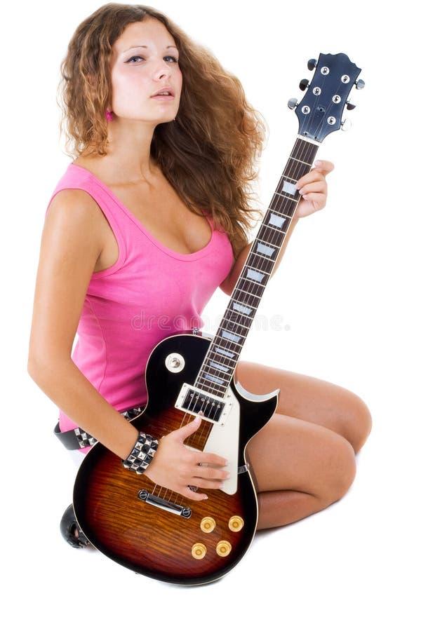 Le beau brunette pose dans le studio avec un guit photographie stock libre de droits