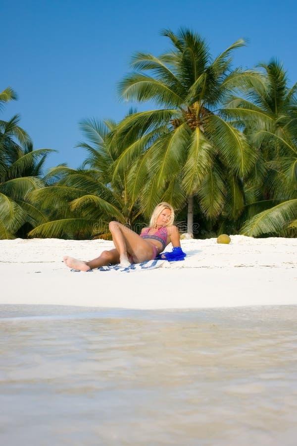 Le beau brunette se trouve sur une plage blanche photo stock