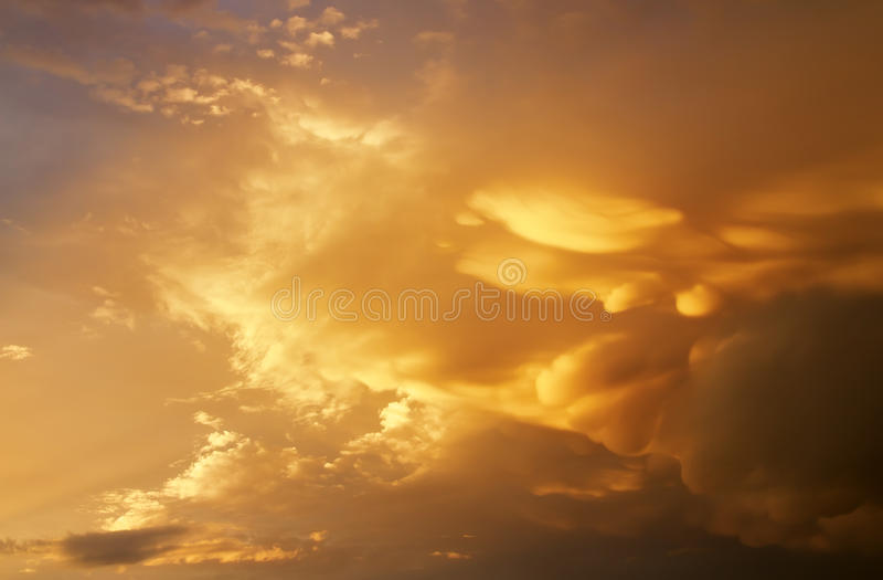 Le beau ciel nuageux pelucheux foncé avec le soleil rayonne photos stock