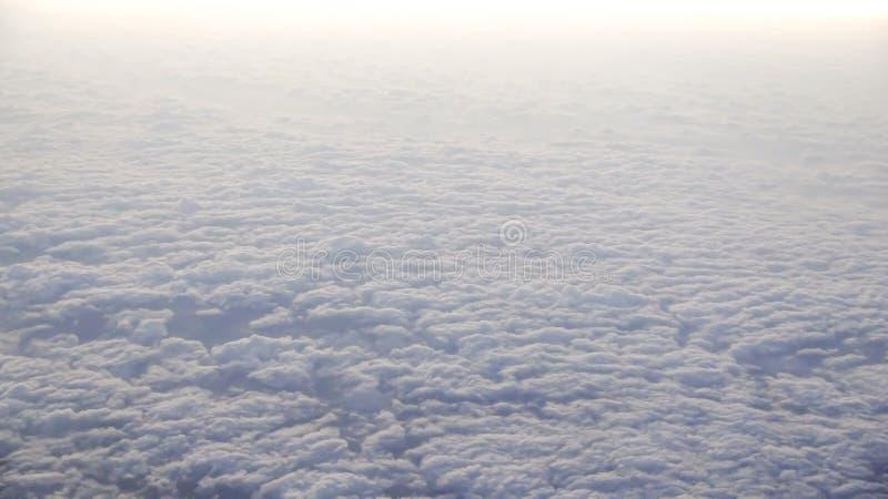 Le beau cloudscape avec le ciel bleu clair Une vue de fenêtre d'avion photos stock