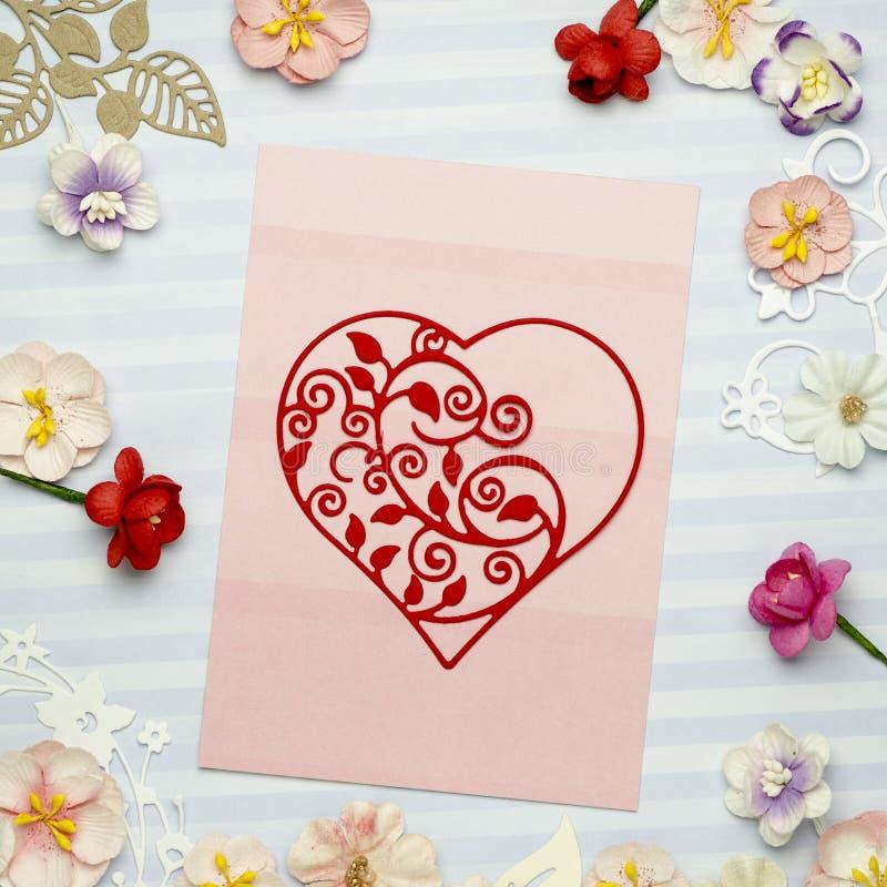 Le beau coeur a fait du papier sur une carte rose, entour? par les fleurs de papier color?es photographie stock libre de droits