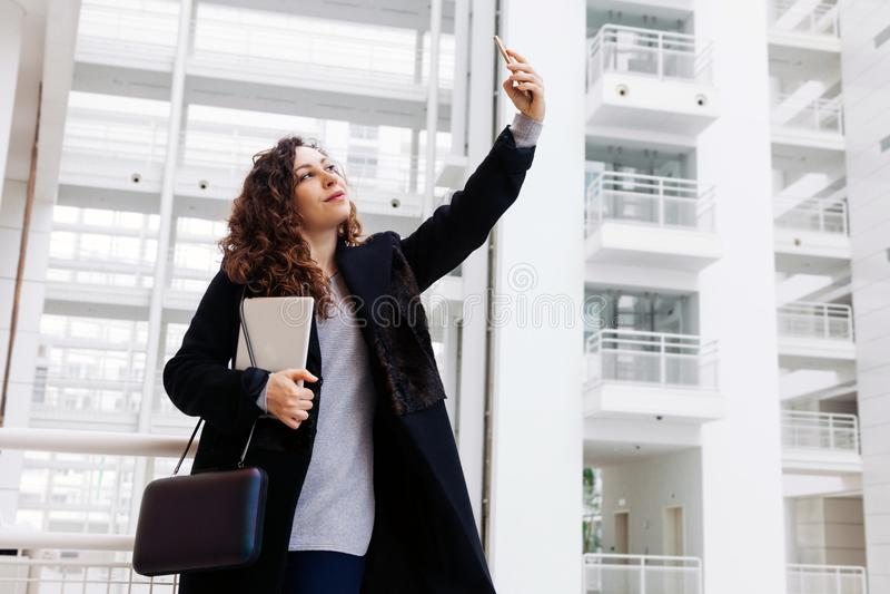 Le beau comprimé blanc de femme d'affaires parlent l'indépendant d'étapes de bureau du directeur d'étudiant de téléphone de burea photos libres de droits