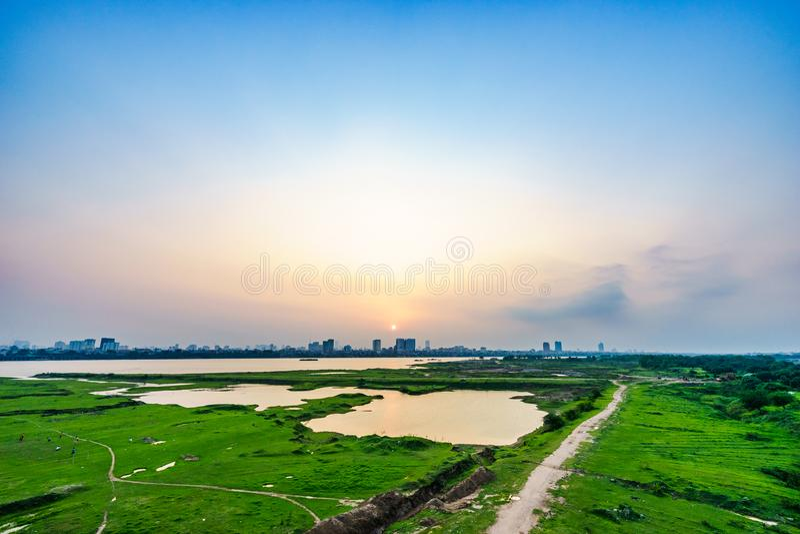 Le beau coucher du soleil à travers la rivière rouge à Hanoï, paysage urbain du Vietnam photo stock