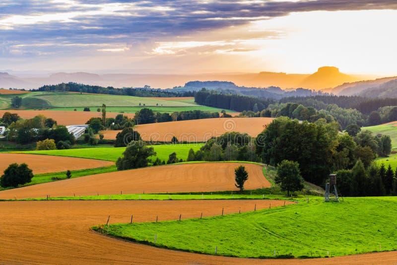 Le beau coucher du soleil au-dessus du paysage de campagne de Rolling Hills avec le soleil rayonne le ciel et le flanc de coteau  photos stock