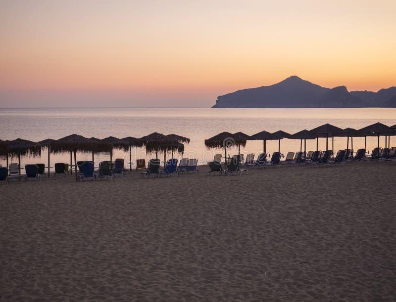 Le beau coucher du soleil orange rose sur la plage d'Agios Georgios Pagon à l'île de Corfou, Grèce avec des parasols vident des l photos libres de droits