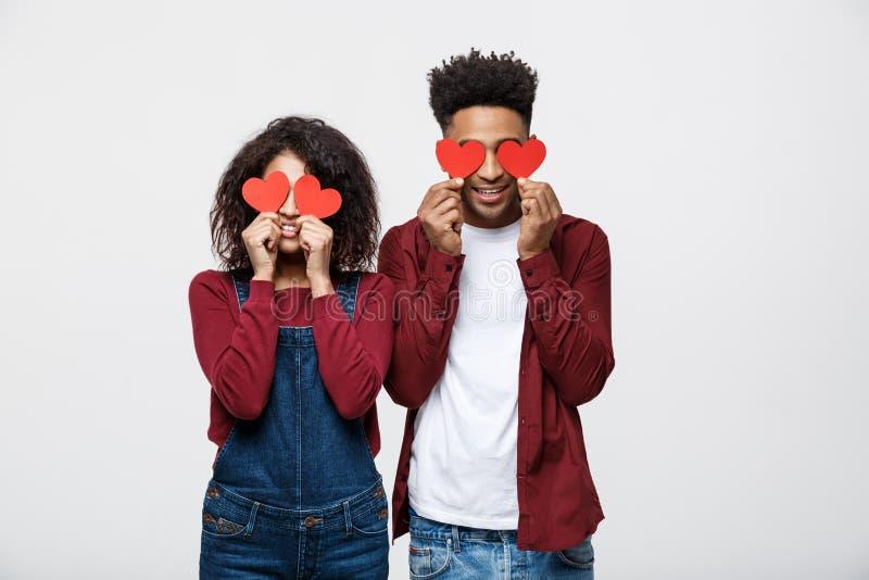 Le beau couple d'Afro-américain d'Afro tient les coeurs de papier rouges et sourit, sur le fond gris photos libres de droits