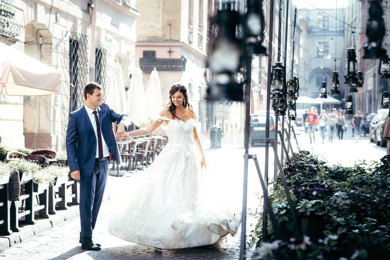 Le beau couple de nouveaux mariés a l'amusement tout en dansant dans la vieille rue ensoleillée de ville photo libre de droits