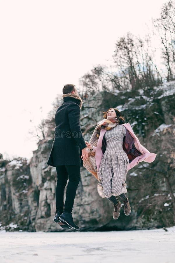 Le beau couple fait de la lévitation au-dessus du lac congelé photographie stock