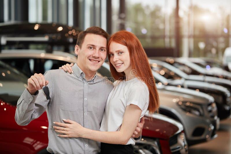 Le beau couple tient la clé de leur nouvelle voiture, regardant l'appareil-photo et le sourire photographie stock libre de droits