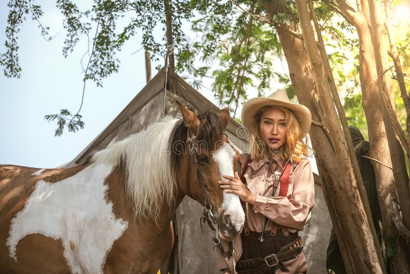 Le beau cowboy asiatique de fille prend soin de son cheval avec soin d'amour photo libre de droits
