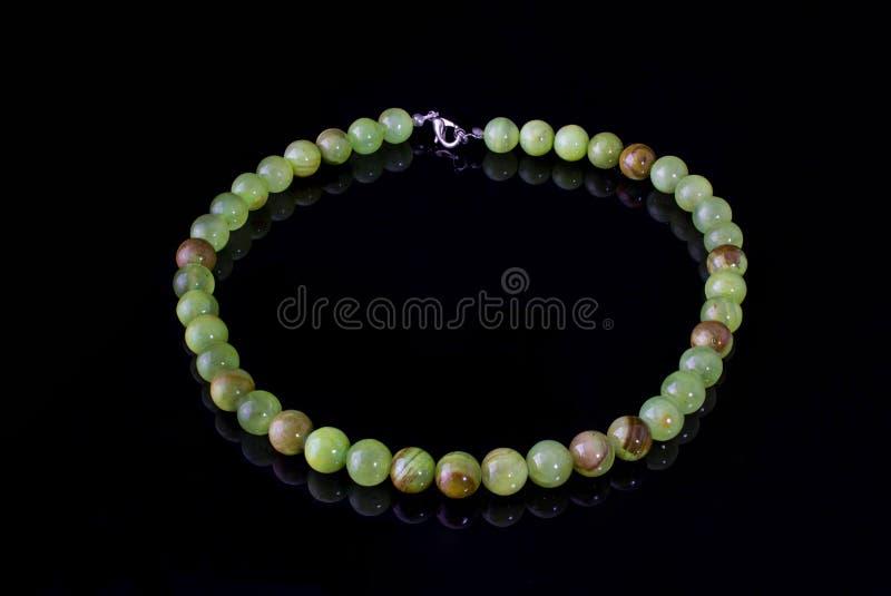 Le beau, de raffinage collier de l'onyx vert perle sur un fond noir images libres de droits