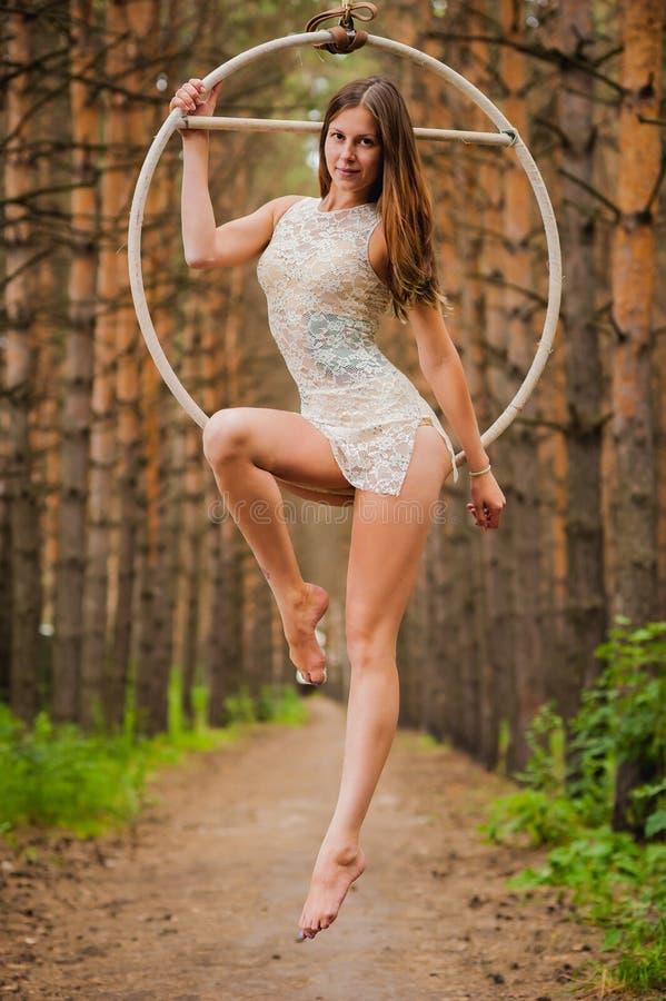 Le beau et gracieux gymnaste aérien exécute des exercices sur l'anneau d'air images stock