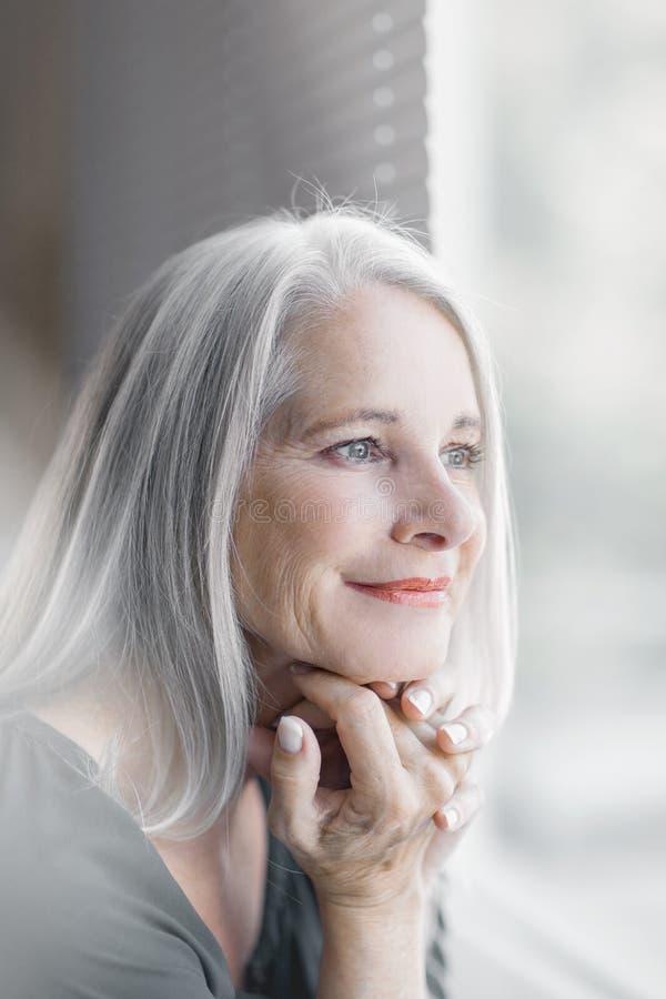 Le beau et plein d'assurance meilleur renversant a vieilli la femme avec les cheveux gris souriant dans l'appareil-photo photographie stock