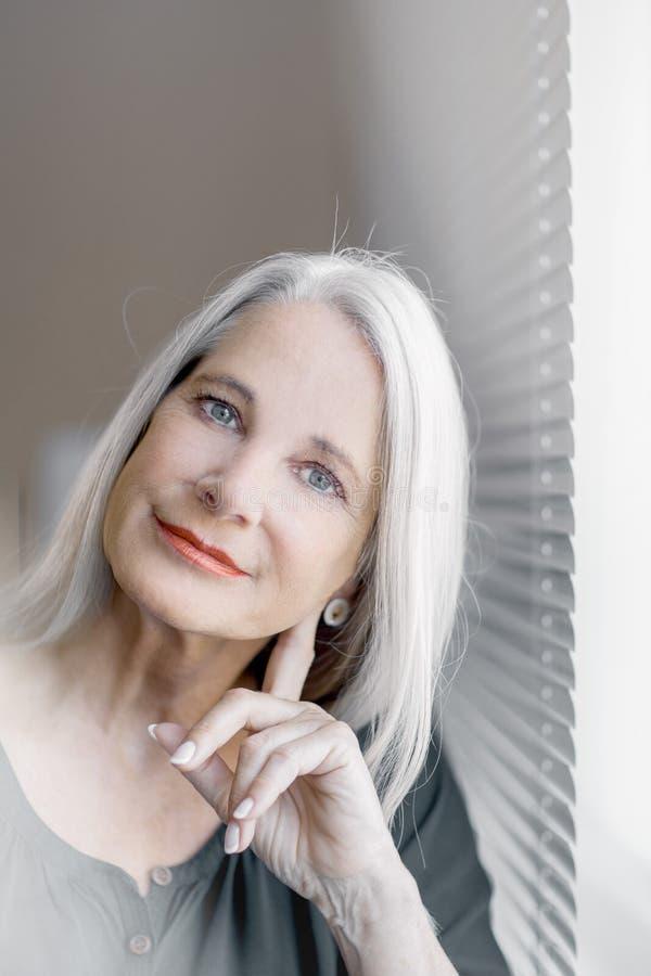 Le beau et plein d'assurance meilleur renversant a vieilli la femme avec les cheveux gris souriant dans l'appareil-photo photos stock