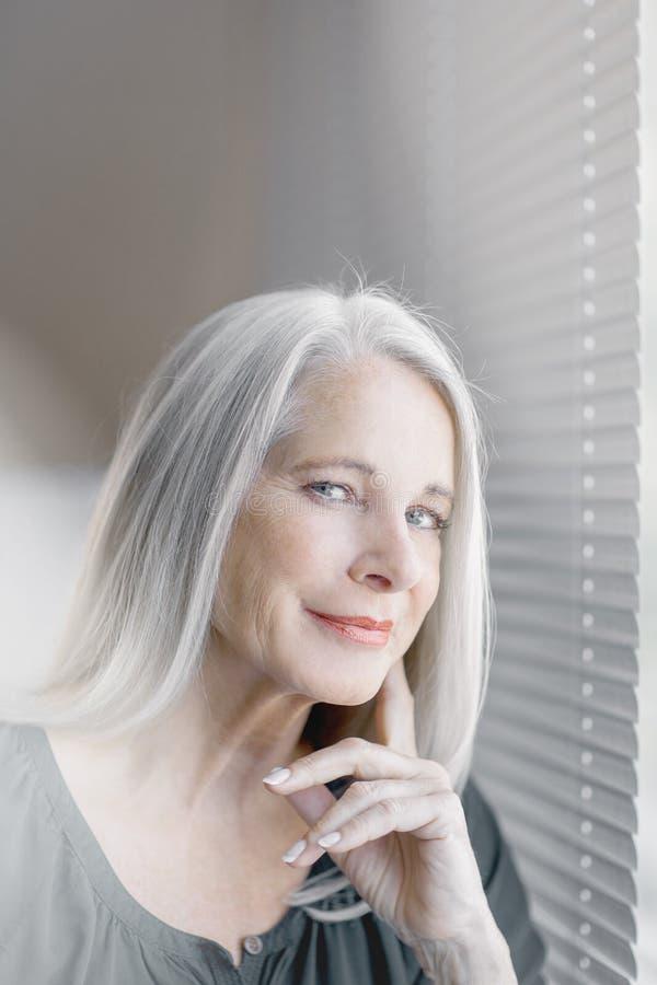 Le beau et plein d'assurance meilleur renversant a vieilli la femme avec les cheveux gris souriant dans l'appareil-photo photo libre de droits