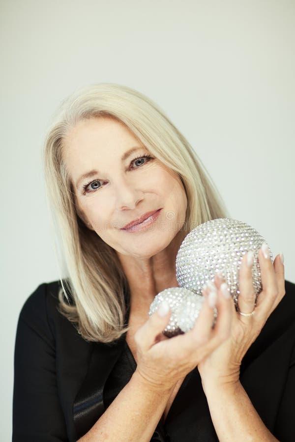 Le beau et plein d'assurance meilleur renversant a vieilli la femme avec les cheveux gris souriant dans l'appareil-photo, tenant  images libres de droits