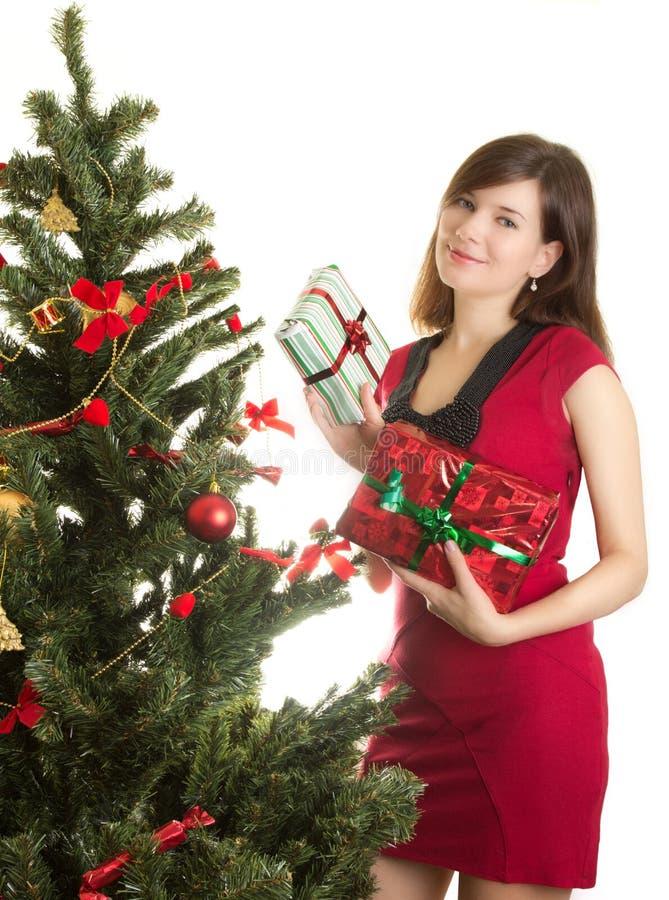 Le beau femme avec des présents s'approchent de l'arbre de Noël photos stock