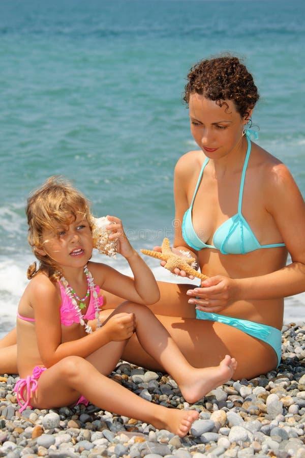 Le beau femme avec la fille s'est penché la cuvette de seashell image libre de droits