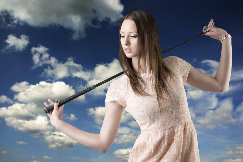 Le beau femme avec le golfclub regarde vers le bas la droite photos stock
