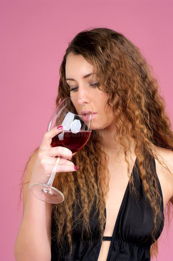 Le beau femme boit du vin rouge photographie stock libre de droits