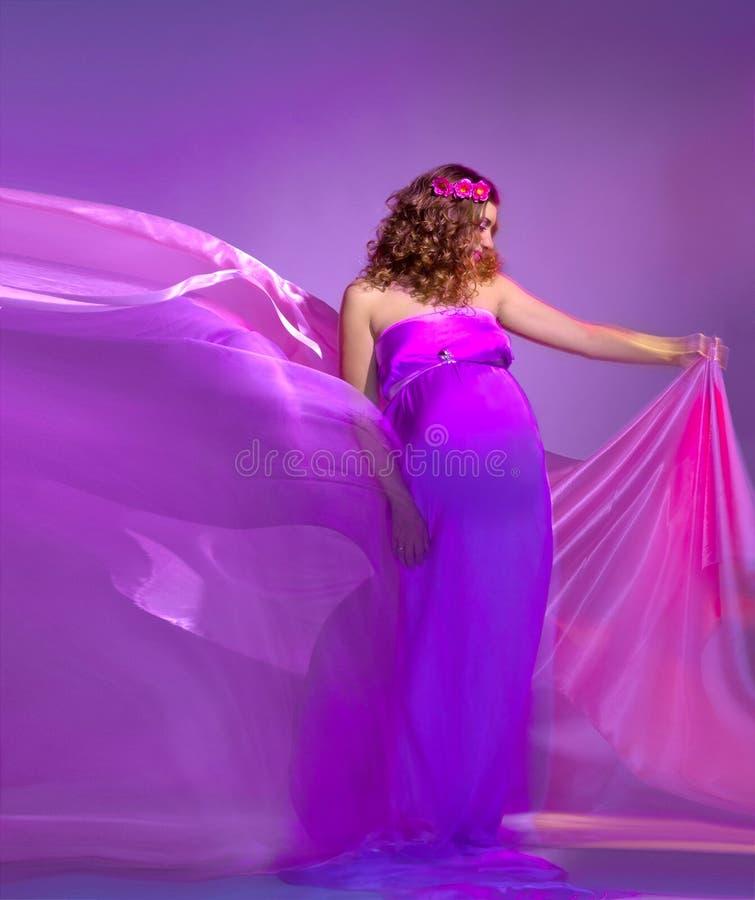 Le beau femme enceinte dans le rose et la violette rectifient photographie stock