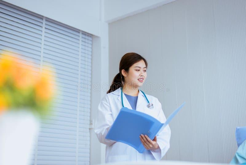 Le beau fonctionnement asiatique de femme de docteur auscultate ou examen patient à l'hôpital photo stock