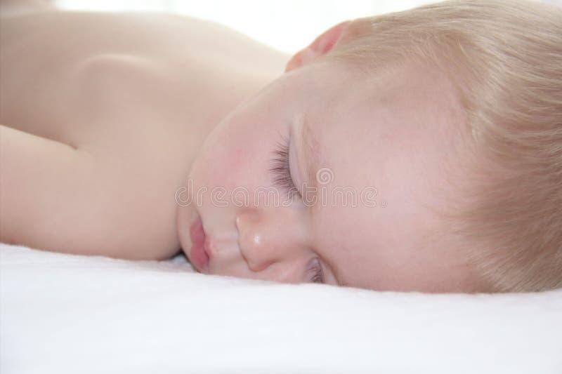 Le beau garçon d'enfant en bas âge dort photos stock