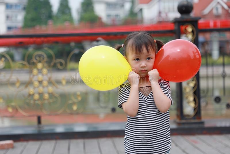 Le beau jeu adorable vilain mignon chinois asiatique de fille avec le ballon et ont l'amusement extérieur dans la promenade heure image libre de droits