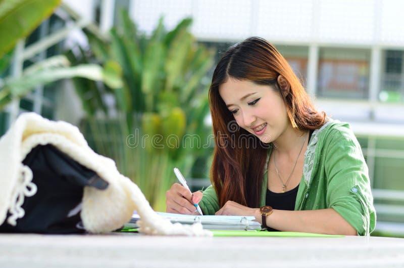 Le beau jeune étudiant asiatique lit et écrit image stock