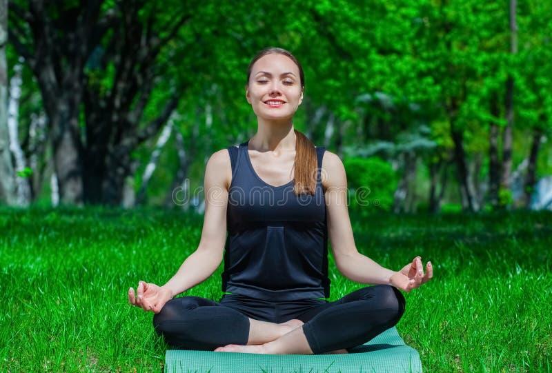Le beau jeune athlète s'assied en position de lotus sur le tapis, dans la nature image stock