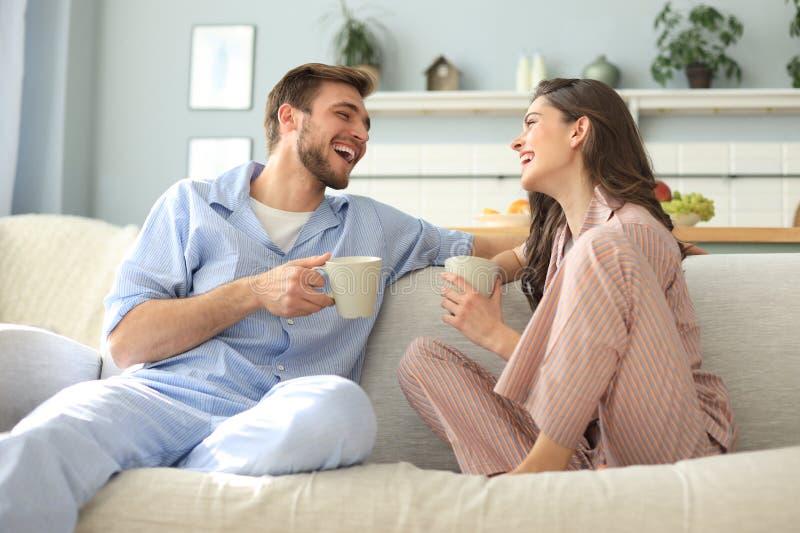 Le beau jeune couple dans des pyjamas regarde l'un l'autre et sourit sur un sofa dans le salon image stock