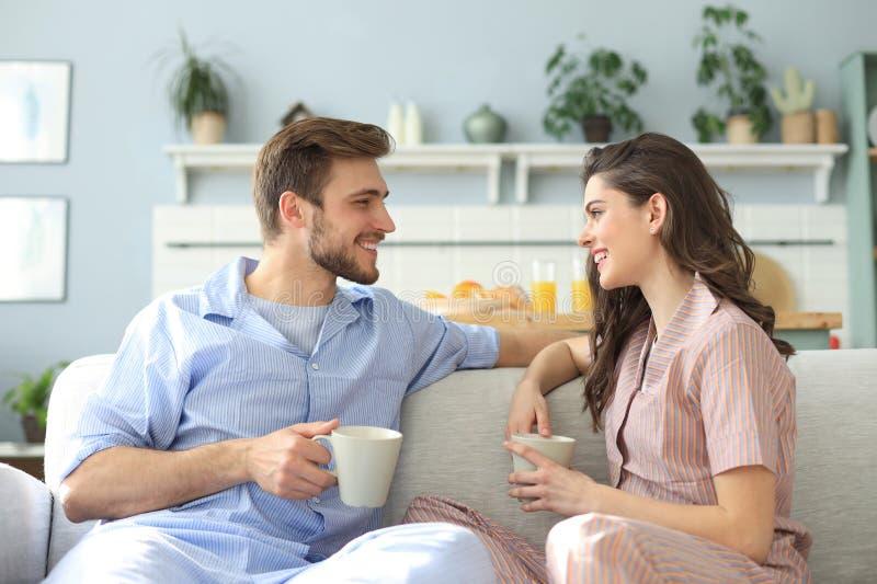 Le beau jeune couple dans des pyjamas regarde l'un l'autre et sourit sur un sofa dans le salon photos libres de droits