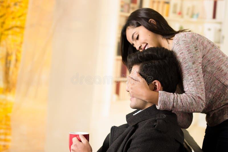 Le beau jeune couple dans l'amour, amie couvre les yeux de son ami à un arrière-plan de bureau images stock