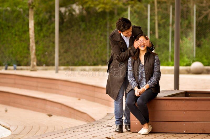 Le beau jeune couple dans l'amour dans le jour de valentines de St, homme couvrant son amie observe en parc images libres de droits