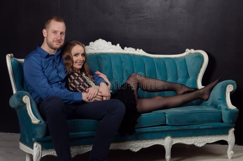 Le beau jeune couple enamouré dans des vêtements classiques se repose sur un bleu photographie stock