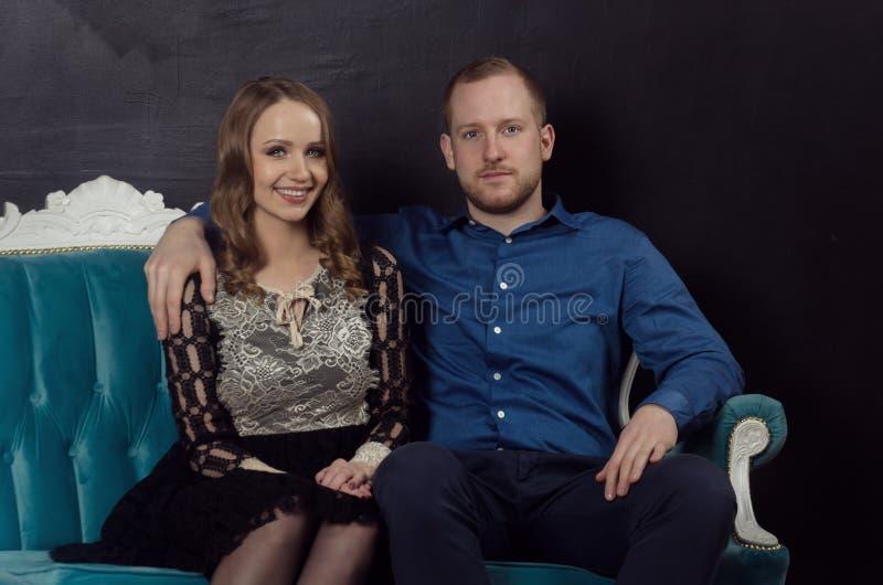 Le beau jeune couple enamouré dans des vêtements classiques se repose sur un bleu image stock