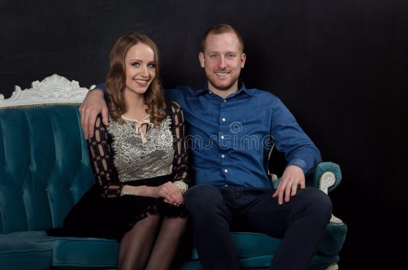 Le beau jeune couple enamouré dans des vêtements classiques se repose sur un bleu photo libre de droits